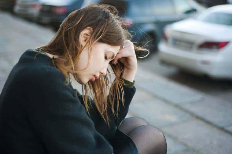erschöpfte Frau, die draußen auf der Straße sitzt