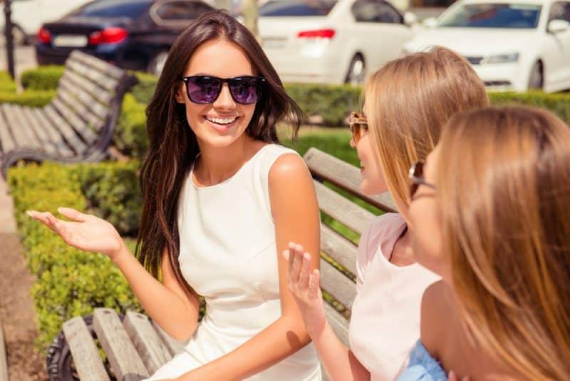 fröhliche Frau, die mit ihren Freunden an der Bank im Park spricht