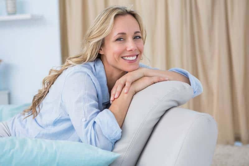 fröhliche hübsche Blondine sitzt auf der Couch zu Hause im Wohnzimmer