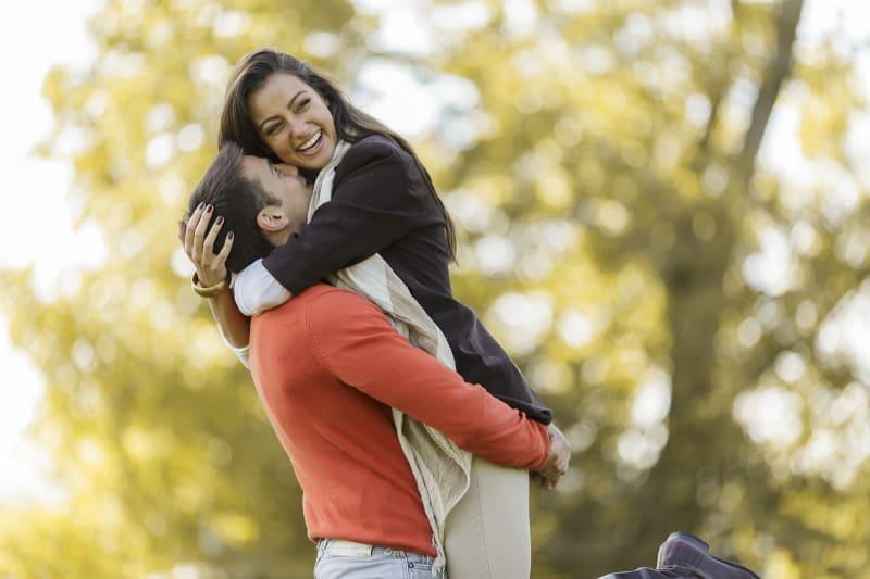 fröhliches Paar, das draußen in der Natur umarmt