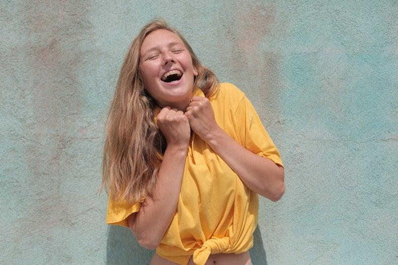 freudige Frau im gelben T-Shirt