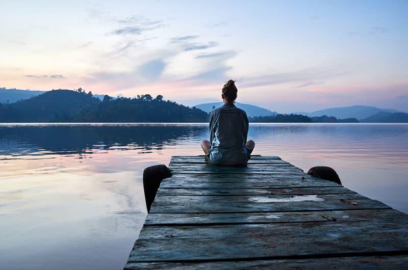 friedliche Frau am See sitzen