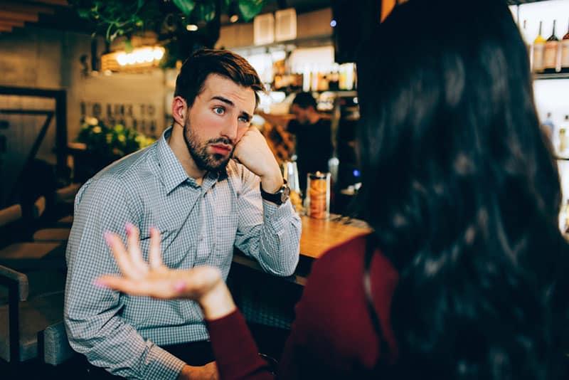 gelangweilter Mann, der Frau in der Kneipe zuhört