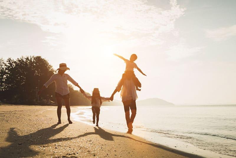 glückliche Familie am Strand spazieren