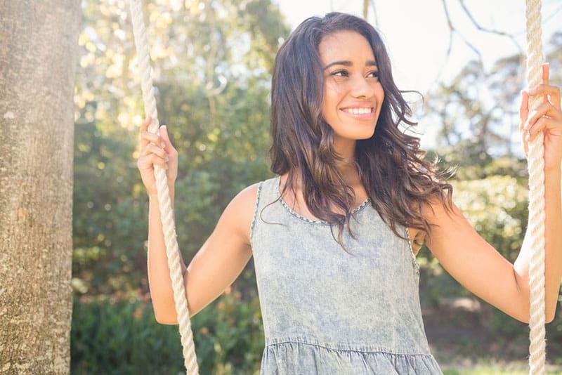 glückliche Frau auf Schaukel im Hof gesetzt