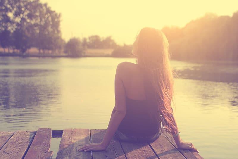 glückliche Frau, die am See sitzt