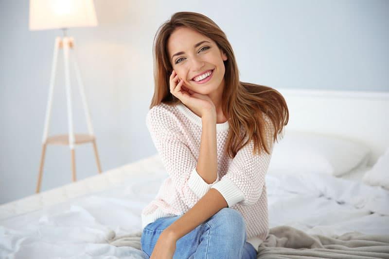 glückliche Frau, die auf dem Bett sitzt und aufwirft