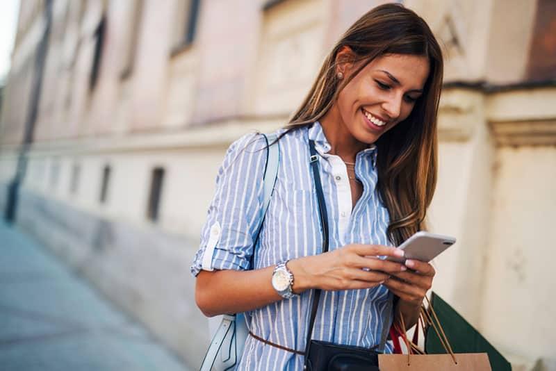 glückliche Frau, die eine Nachricht am Telefon schreibt