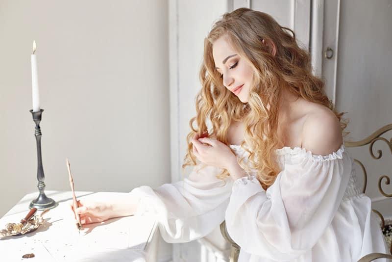 glückliche Frau, die einen Liebesbrief schreibt