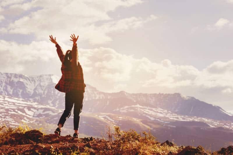 glückliche Frau, die ihre Hände auf Berg erhebt