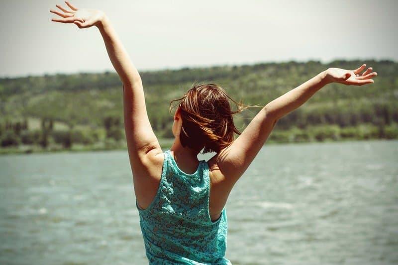 glückliche Frau die in den Fluss schaut