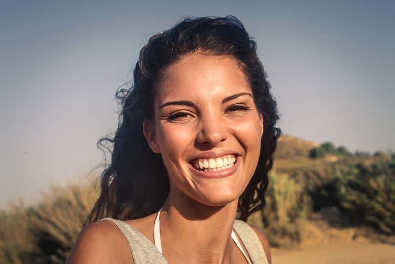 glückliche Frau, die in die Kamera lächelt