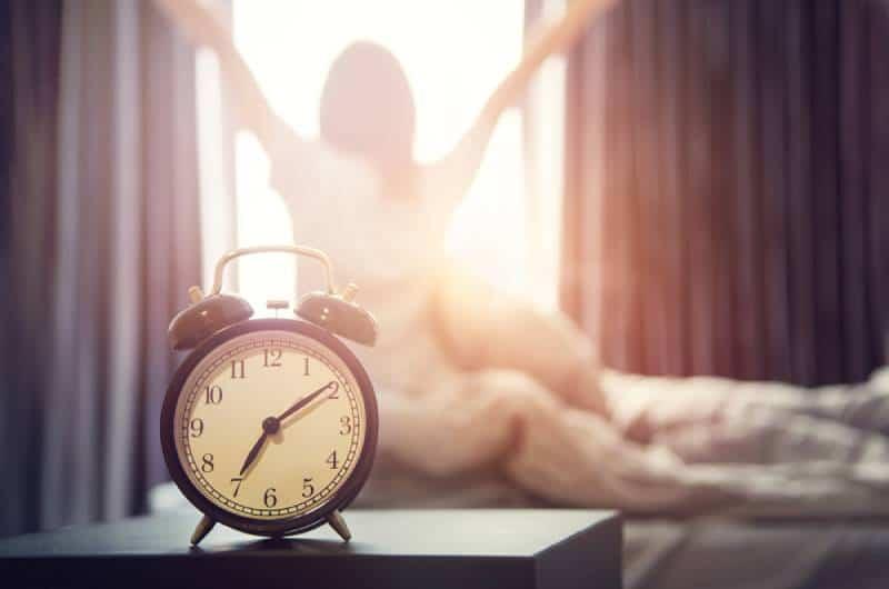 glückliche Frau, die sich nach dem Aufwachen im Bett ausdehnt, Sonnenlicht am Morgen