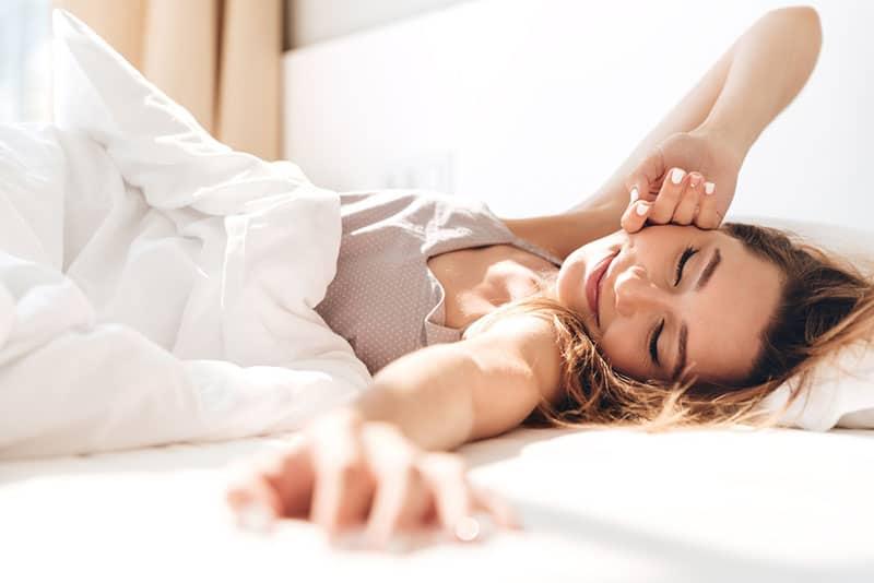 glückliche Frau im Bett liegend