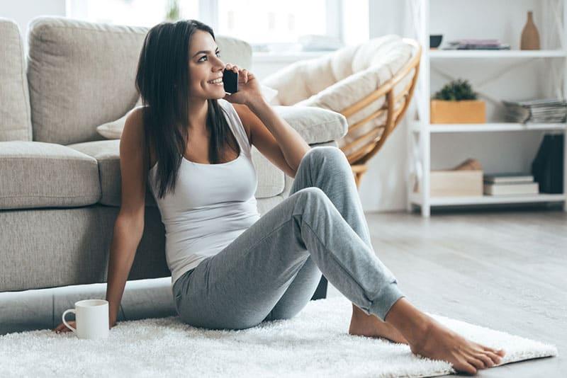 glückliche Frau im Trainingsanzug, die am Telefon spricht