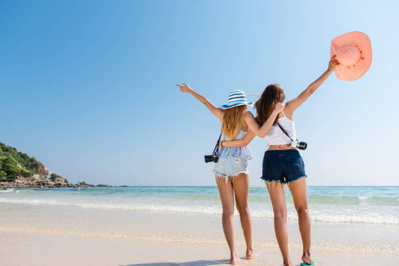 glückliche Freunde, die ihre Hände am Strand heben