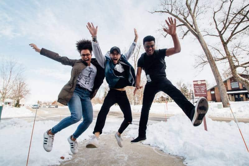 glückliche Freunde springen auf die Straße