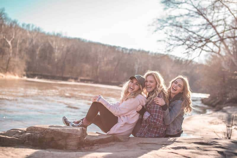 glückliche Freundinnen sitzen am See