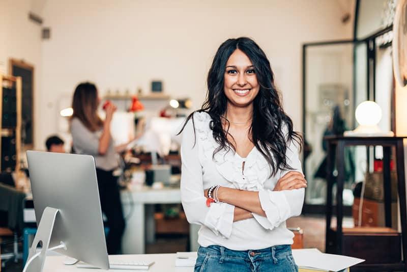 glückliche Geschäftsfrau, die im Büro aufwirft