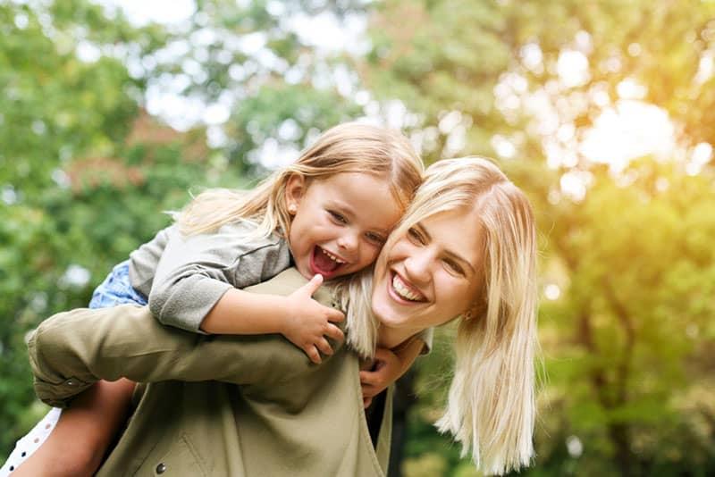 glückliche Mutter, die ihr kleines Mädchen trägt