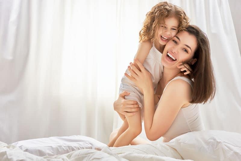 glückliche Mutter im Bett mit ihrem kleinen Mädchen