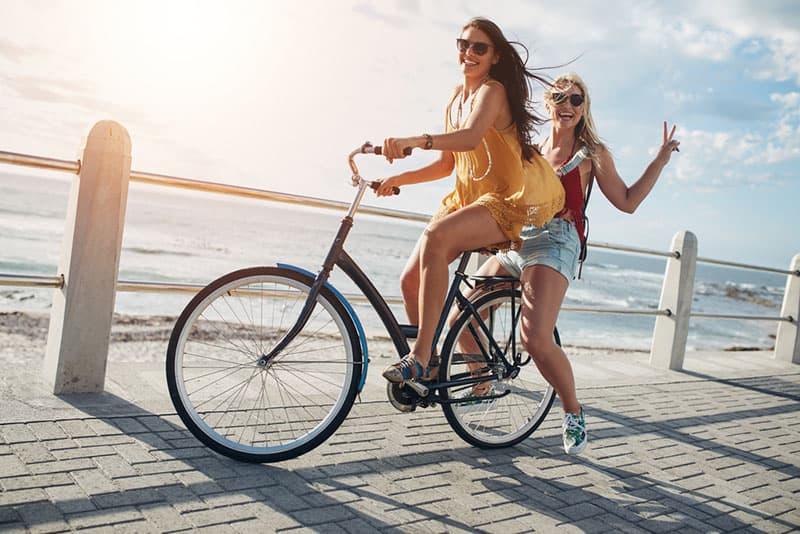 glückliche Schwestern, die zusammen Fahrrad fahren