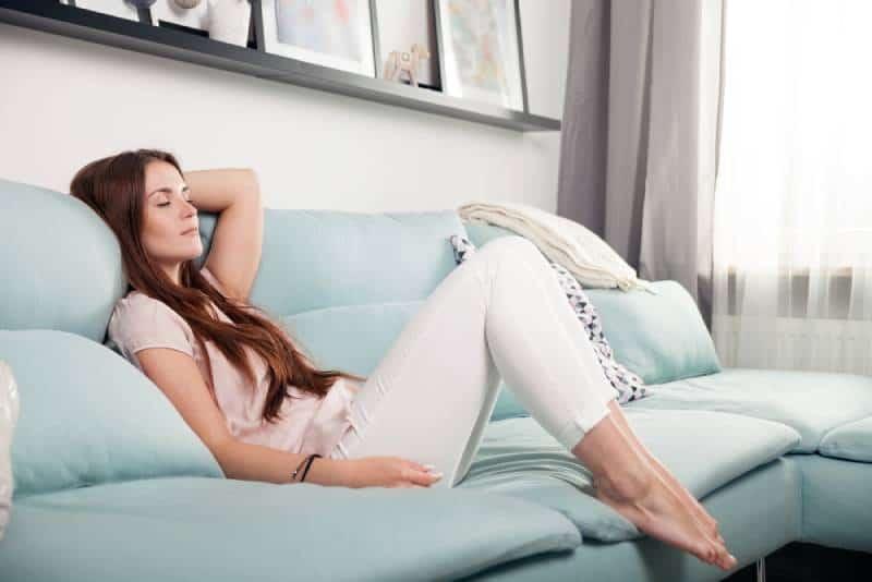 glückliche junge Frau, die im Wohnzimmer liegt und sich entspannt