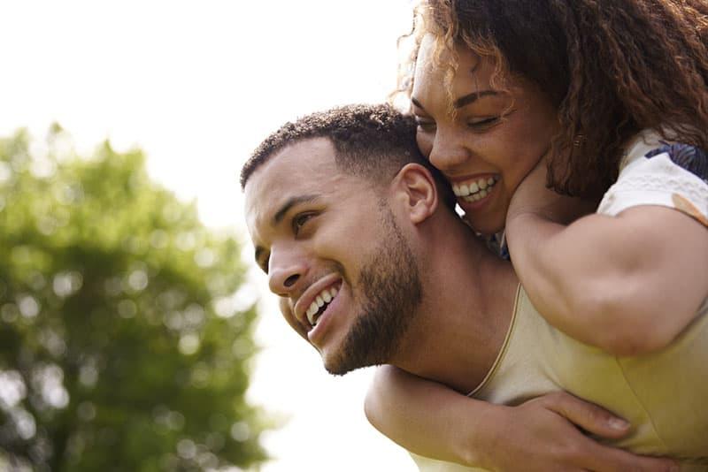 glücklicher Mann, der eine Frau auf seinem Rücken trägt
