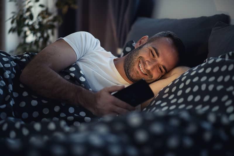 glücklicher Mann, der während der Nacht auf seinem Telefon tippt