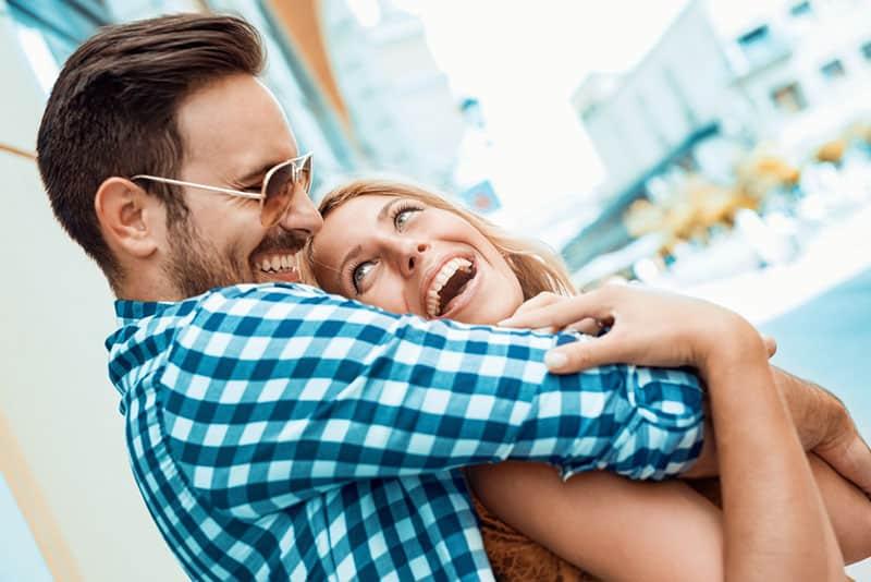 glücklicher junger Mann, der sein Mädchen umarmt