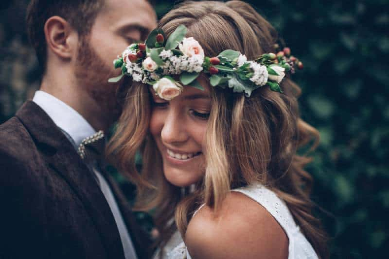 glückliches Hochzeitspaar. Braut mit Blumen im Haar.