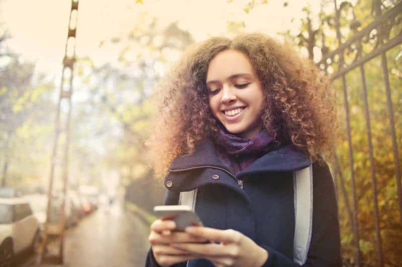 glückliches Mädchen, das ihr Telefon draußen betrachtet