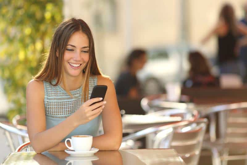glückliches Mädchen, das ihr Telefon im Café betrachtet