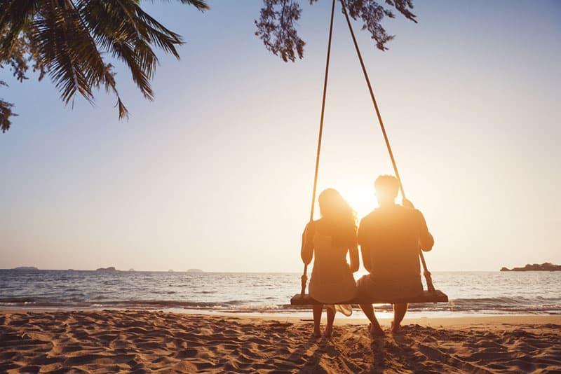 glückliches Paar auf Schaukel im Sonnenuntergang