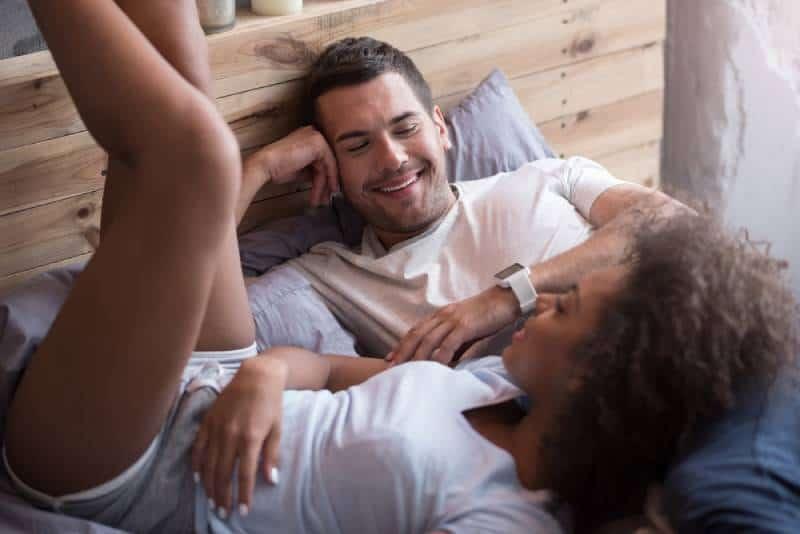 glückliches Paar auf dem Bett liegen und reden
