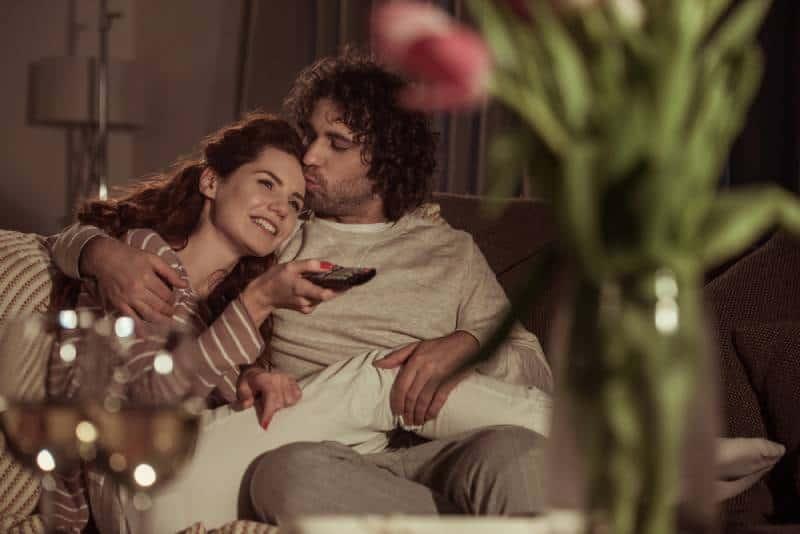 glückliches Paar, das abends auf dem Sofa fernsieht