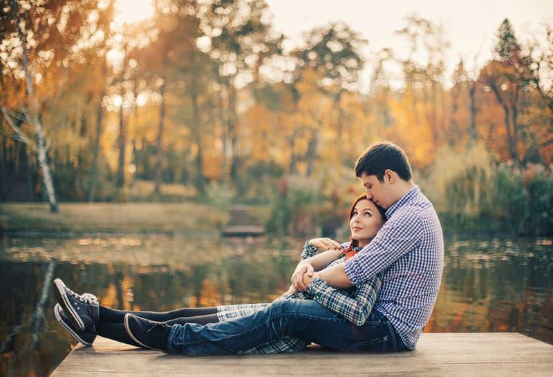 glückliches Paar, das am See kuschelt
