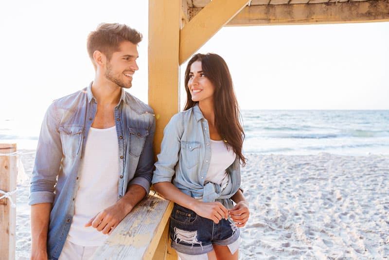 glückliches Paar, das auf dem Sand steht