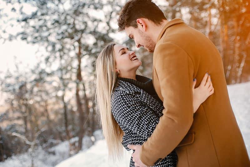 glückliches Paar, das draußen auf dem Schnee steht