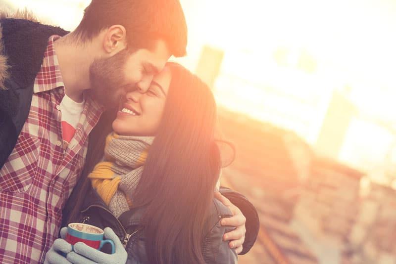 glückliches Paar, das draußen kuschelt