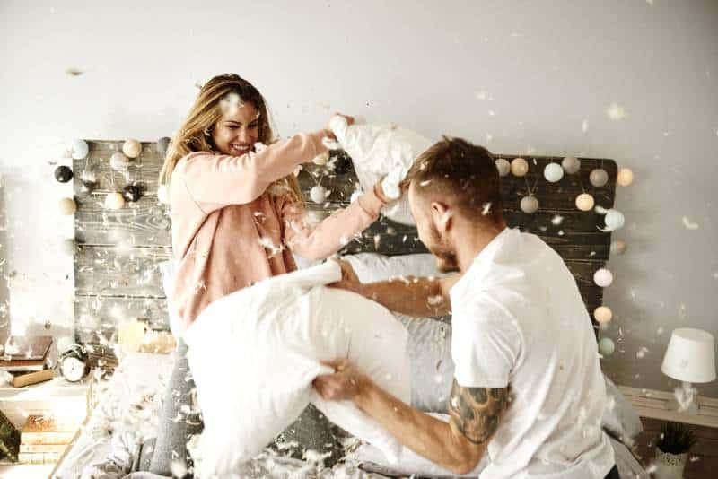 glückliches Paar, das eine Kissenschlacht hat