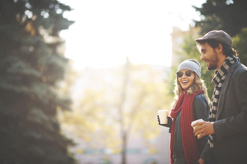 glückliches Paar zu Fuß und Kaffee trinken