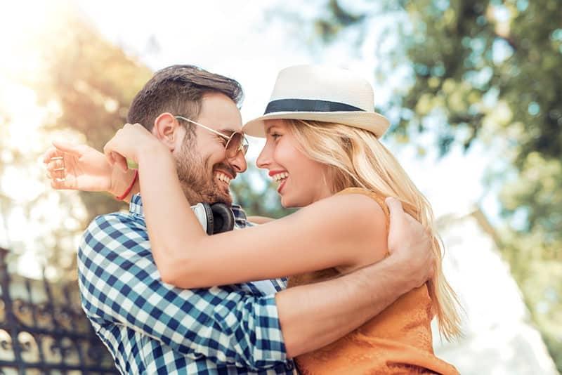 glückliches junges Paar, das im Park umarmt