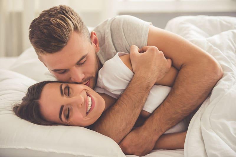 gutaussehender Mann, der seine Frau im Bett umarmt und küsst