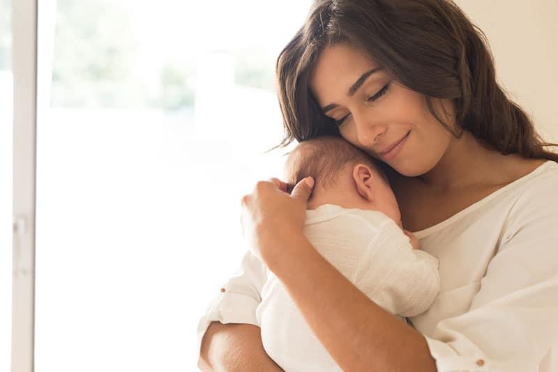 hübsche Frau, die ein Baby hält