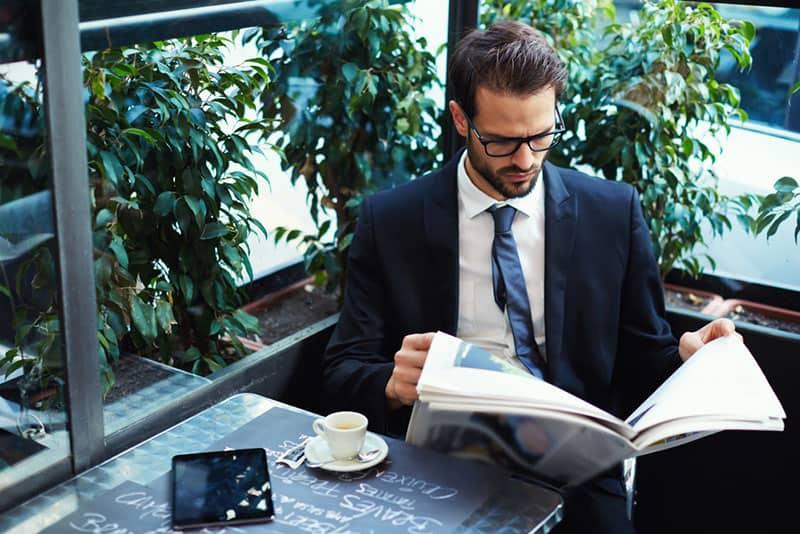 hübscher Geschäftsmann, der eine Zeitung liest