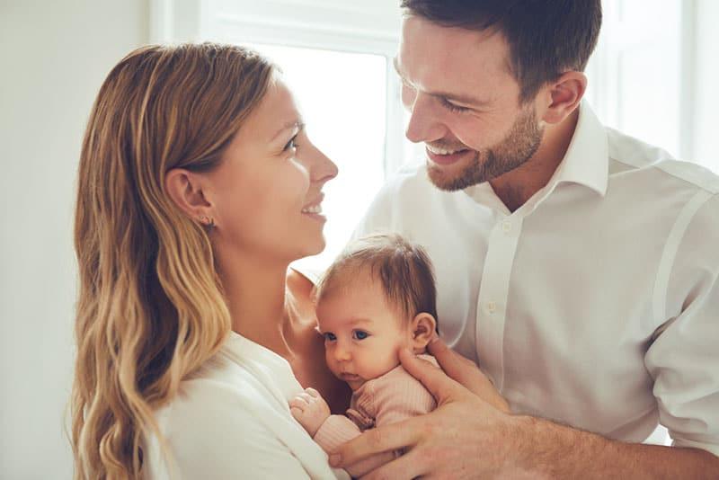 junge Eltern halten ihr Baby
