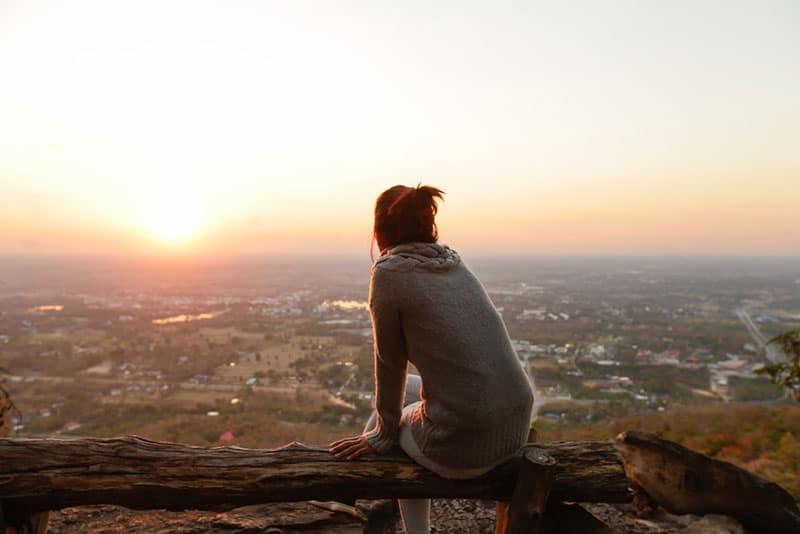 junge Frau, die allein auf der Stadtansicht sitzt