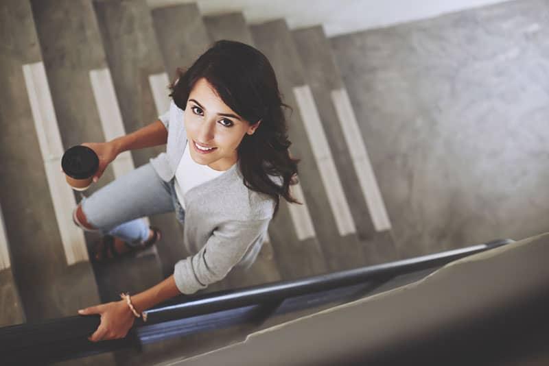 junge Frau, die auf Treppen klettert