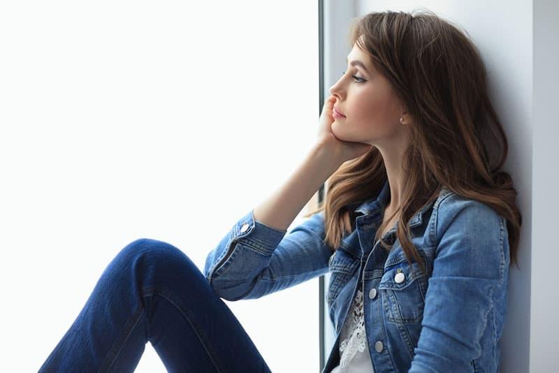 junge Frau, die draußen am Fenster sitzt